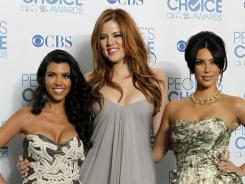 Kourtney, left,  Khloe and Kim Kardashian pulled their endorsement of a prepaid debit card that drew criticism for its high fees.