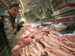 Customers peruse the meat selection at a shop on Jan. 17, 2012, in Shanghai.