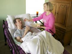 Linda Morgan feeds breakfast to husband Michael, who is bedridden with Alzheimer's, at their home in Lehigh Acres, Fla.