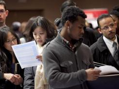 People wait to talk with potential employers at a job fair sponsored by National Career Fairs in New York on Dec. 12.
