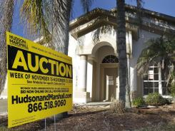 An auction signs sits in front of a foreclosed home in Valrico, Fla., in November 2010.