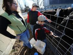 Samantha Walter, 35, watches as her sons Austin, 14, and Dalton, 8, feed livestock at their farm in Grand Ridge, Ill.