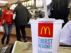 The McDonald's logo is displayed on a drink as customers purchase lunch at McDonald's, in Springfield, Ill., on Jan. 20, 2012.