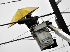 A lineman for Verizon shields himself from the rain as he works on a phone line on East Broad Street in West Hazleton, Pa., on Jan. 17, 2012.
