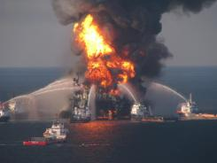This April 21, 2010, file photo shows fire crews battling the remnants of the offshore oil rig Deepwater Horizon.