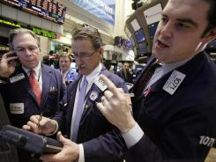 Traders on the floor of the New York Stock Exchange on Jan. 25, 2012, upon hearing the Federal Reserve plans no interest rate hikes until late 2014.