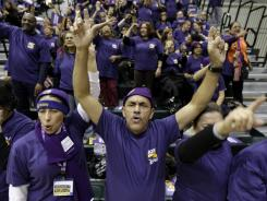 Manuel Lantigua, center, cheers with a crowd of office cleaners from Local 32BJ of the Service Employees International Union during a rally in December 2011 in Newark, N.J., about new contract negotiations.