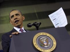 President Obama holds up a proposed mortgage application form as he speaks at the James Lee Community Center in Falls Church, Va., on Feb. 1, 2012.