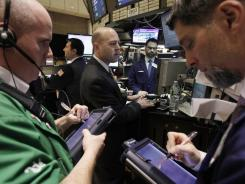 Stock specialist Jay Woods, center, works at his post on the floor of the New York Stock Exchange on Feb. 1, 2012.