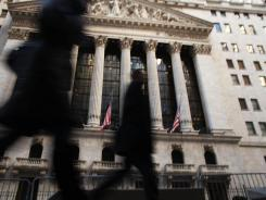 People walk by the New York Stock Exchange on Friday.