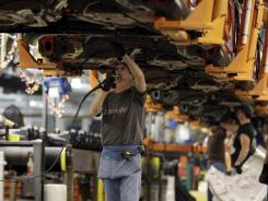 A line worker assembles a Ford Focus at the company's Michigan Assembly plant in Wayne, Mich.