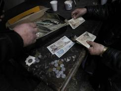 A curio seller shows a customer some old 1,000-drachma bills used before Greece's adoption of the euro currency at an outdoor market in Athens, on Feb. 6, 2012.
