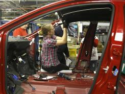 An auto worker assembles parts on the 2013 Dodge Dart at the Chrysler Plant in Belvidere, Ill., on Feb. 2, 2012.