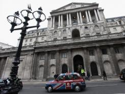 A taxi drives past the front of the Bank of England in London's financial district.