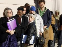 People wait in line to enter a job fair employer hiring event for Safeway, in Portland, Ore., in January 2012.