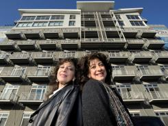 Twins Linda, left, and Debra Basili at the building in Chicago's West Loop where they bought two investment condos a year ago.