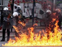 A firebomb explodes at riot police during a 48-hour general strike in Athens on Friday as Greek citizens protest new austerity measures.