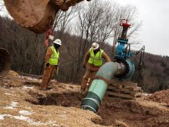 A Cabot Oil and Gas crew works on a natural gas valve at a hydraulic fracturing site in South Montrose, Pa., in January 2012.