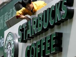A worker cleans the sign outside one of the many Starbucks outlets in Beijing.