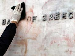 A worker cleans red and black paint off the sign of the Bank of Greece after Sunday's riots in Athens.