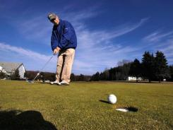 Jim Loomis sinks a putt Jan. 31 on a sunny and mild day at Glen Oak Country Club in Waverly, Pa.