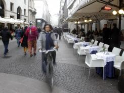 A woman rides past empty tables outside a cafeteria in Milan, Italy in November.