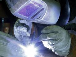 A workman welds a stainless steel tank at JV Northwest, in Camby, Ore. The company makes stainless steel vessels.