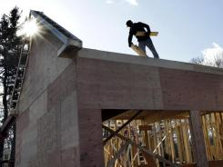 A builder works on a new single-family home in North Andover, Mass., on Feb. 13, 2012.
