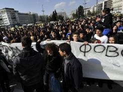 High schools students carry a banner reading 'we break the fear' and chant 'bread-education-freedom' in front of the Parliament building in Athens Feb. 17, 2012.