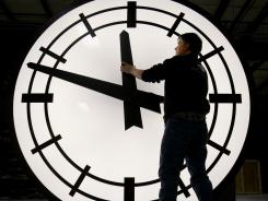 Machinist Scott Gow prepares to remove the hands of an eight-foot clock being shipped to Ashley Furniture in Kenosha, Wis., from the Electric Clock factory in Medfield Mass. January's index of leading economic indicators was led by a rise in the average manufacturing workweek, among other components.