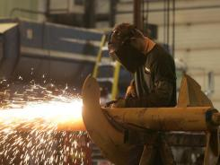 An employee at Sioux Automation in Sioux Center grinds an auger shaft.
