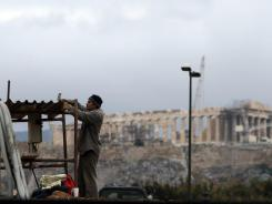 A worker hammers at a construction site of a new car parking area for a metro station as the ancient Acropolis hill is seen in the background in Athens in February 2012.