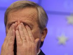Luxembourg's Prime Minister Jean-Claude Juncker rubs his face after a 12-hour meeting of eurozone finance ministers at the EU Council building in Brussels on Tuesday, Feb. 21, 2012.