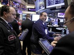 Traders and stock specialists on the floor of the New York Stock Exchange on Feb. 17, 2012. Global markets reacted cautiously Feb, 21 to Greece finally securing a second massive bailout in less than two years.