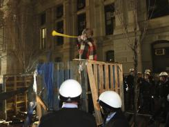 "A protester blows a horn Nov. 30 as police officers surround his shelter at the ""Occupy"" encampment in Philadelphia."