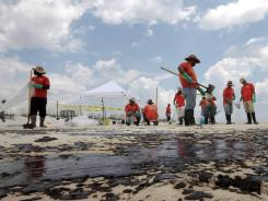 A crew hired by BP picks up oil on the beach in Gulf Shores, Ala., on July 2, 2010.