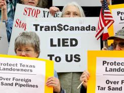 Protesters hold signs opposing the TransCanada Keystone Pipeline on Feb. 17 in Paris, Texas.