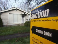 A auction sign in front of a home in Salem, Ore., on Feb. 23, 2012.