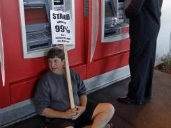 A demonstrator sits in front of an ATM during a Nov. 2 protest in Oakland, Calif.