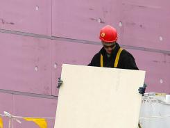 A worker labors on the rooftop of a commercial building going up in downtown Cleveland in February 2012.