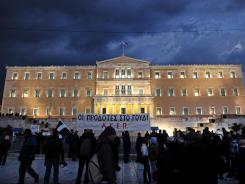 People walk outside the Greek parliament in Athens Feb. 29, 2012.