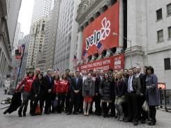 Executives, employees and guests of Yelp pose in front of the New York Stock Exchange March 2, 2012, before Yelp's stock market debut.