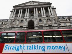 A bus drives past the Bank of England in London's financial district.