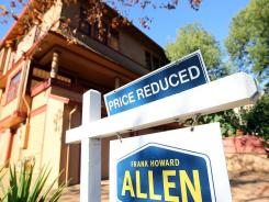 "A ""price reduced"" sign is posted in front of a home in San Rafael, Calif."