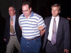 Daniel Stephen Wiant, center, is led to an intake facility in Columbus, Ohio, by officers in 2000.