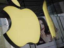 The company's logo sign hangs in an Apple shop in Shanghai.