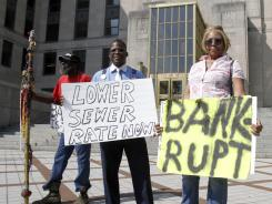 Joe Minter, Harry Turner, and Mabel Nunn, from left, protest outside the Jefferson County courthouse as Jefferson County commissioners meet about the county's bankruptcy in Birmingham, Ala. on Aug. 12, 2011.