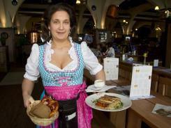 Waitress Nicole Wild with Nurnberger Rostbratwurst at the Berlin restaurant Hofbrau Munchen.