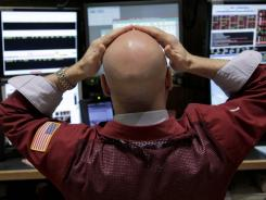 A trader studies monitors on the floor at the New York Stock Exchange on March 6, 2012.