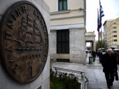 People walk past a monument featuring a replica of the last edition of the Greek currency, the drachma, in the center of Athens on Feb. 29.